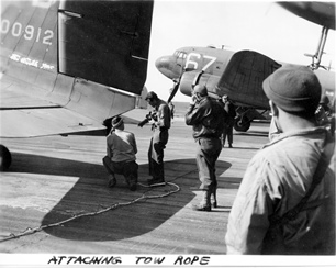 Signal Corps photo of men attaching wire-on-tow-line to C-47 for Market mission or the Varsity mission